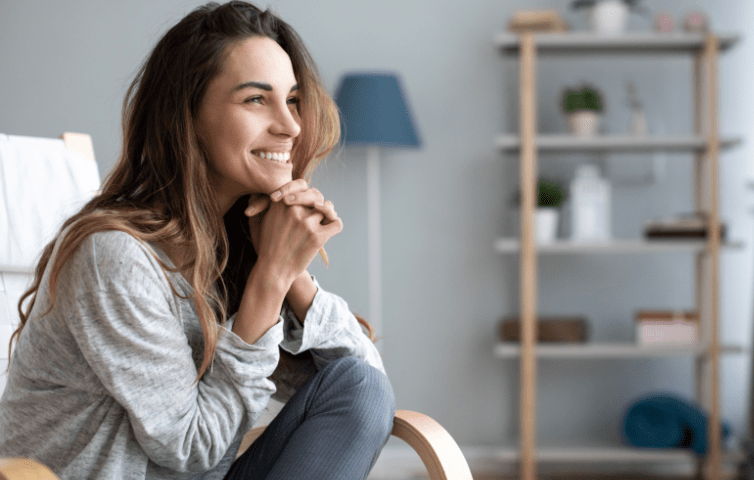 Girl smiling sitting on chair in modern apartment