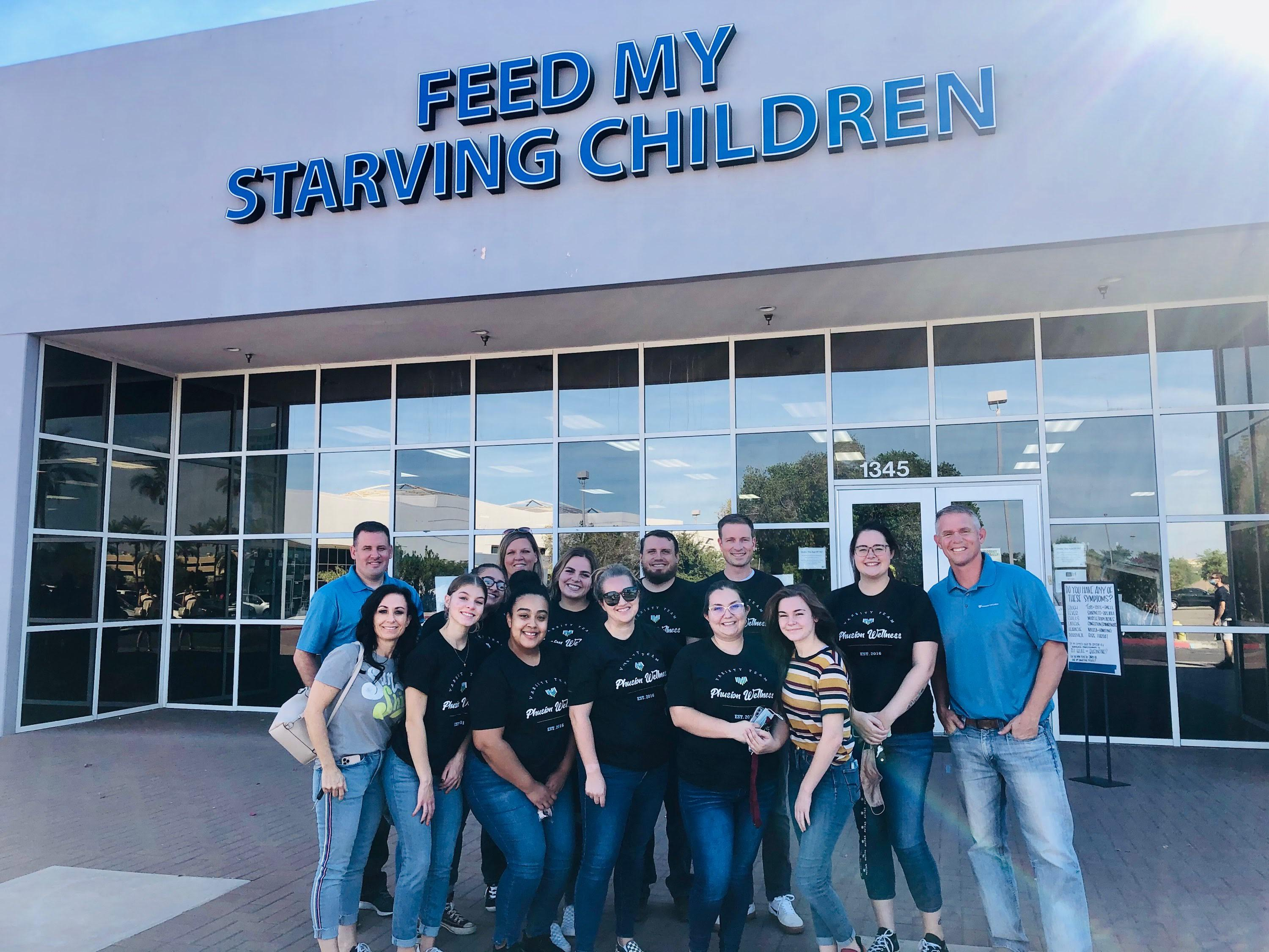 Phusion Wellness team standing outside feed my starving children building