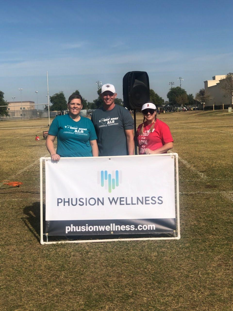 Phusion Wellness team standing infront of Phusion Wellness banner